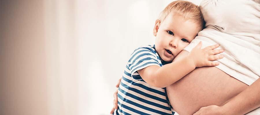 bebê abraçando mãe grávida